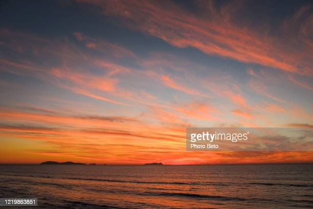 ein bewölkter und bunter sonnenuntergang an der pazifikküste mexikos - sonnenuntergang stock-fotos und bilder