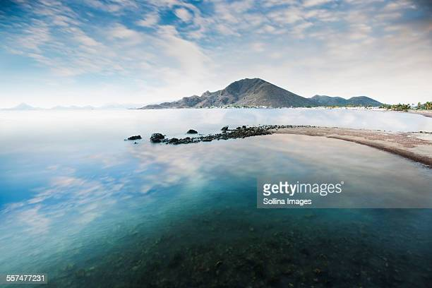 Cloudy blue sky reflecting in lake