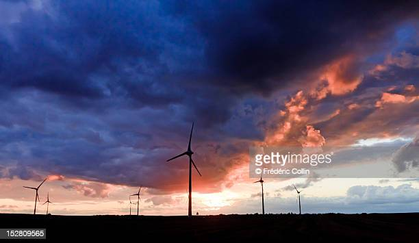 Cloudy colorful sunset over wind turbines