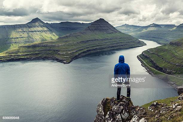 Cloudy day at faroe islands, a man in blue jacket is watching away