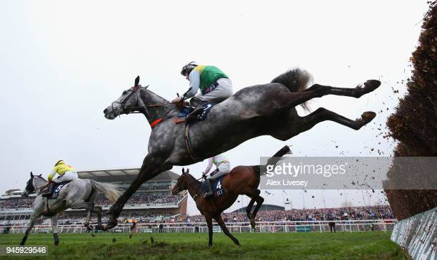 Cloudy Dream ridden Brian Hughes clears a fence during the JLT Melling Chase on Ladies Day at Aintree Racecourse on April 13 2018 in Liverpool England