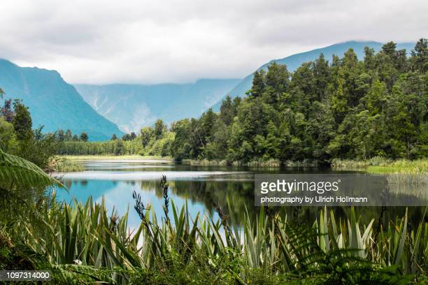 cloudy lake matheson, south island, new zealand - lush stock pictures, royalty-free photos & images