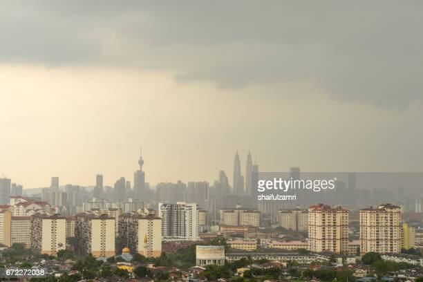 cloudy moments of downtown kuala lumpur with petronas twin towers and kl tower dominant the skyline. - shaifulzamri stockfoto's en -beelden