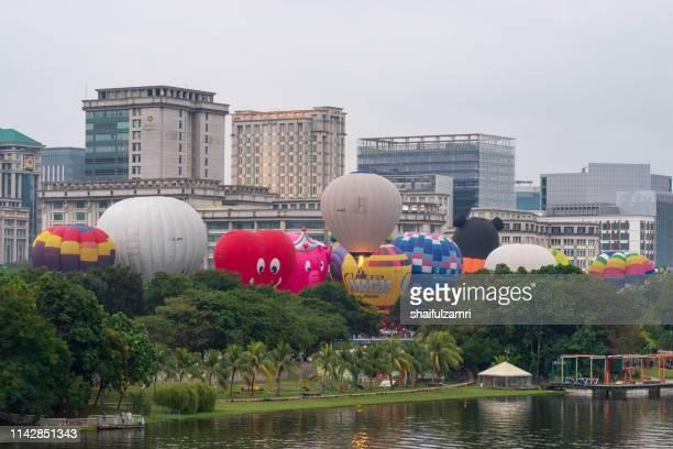 cloudy morning view with hot balloons over lake putrajaya, malaysia. - shaifulzamri stock pictures, royalty-free photos & images