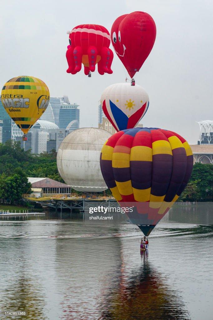 Cloudy morning view with hot balloons over lake Putrajaya, Malaysia. : Stock Photo