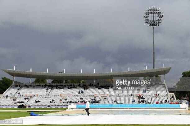 Cloudy skies hang over the covered pitch as play is delayed by rain on the fifth day of the first Test match between England and India at the Trent...