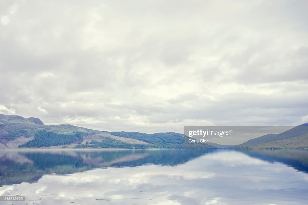 Cloudy sky and hilly landscape reflected in still lake : Foto stock