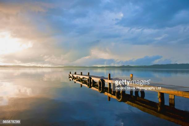 Cloudy sky and wooden dock reflecting in remote lake