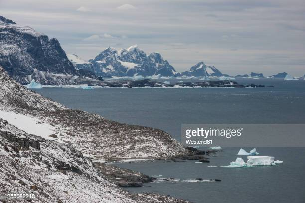 cloudy sky over coastline of coronation island - antarctic ocean stock pictures, royalty-free photos & images