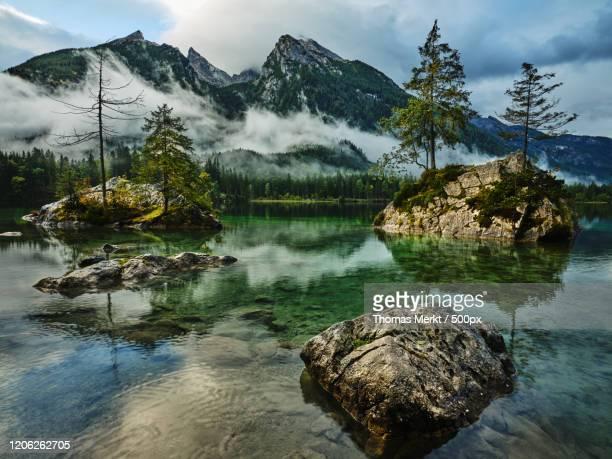 cloudy sky over foggy mountain range and lake, hintersee lake, ramsau, bavaria, germany - images stock-fotos und bilder
