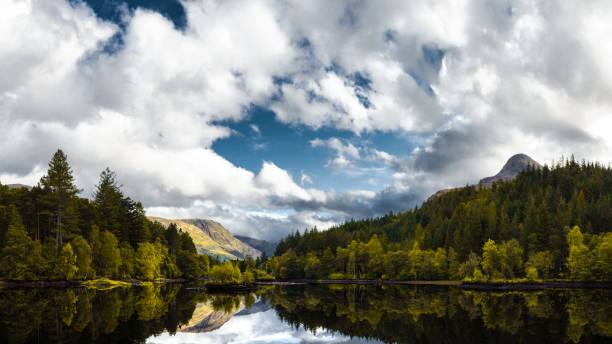Cloudy sky over forest, mountain and lake, Glencoe Lochan, Fort William, Scotland, UK