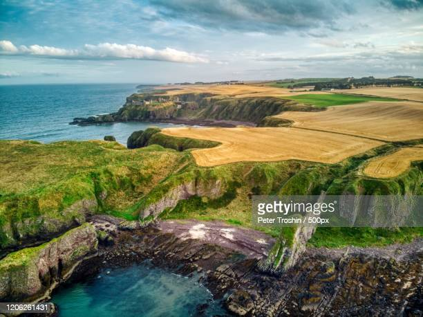 cloudy sky over rocky coastline and wheat fields, stonehaven, uk - aberdeenshire stock pictures, royalty-free photos & images