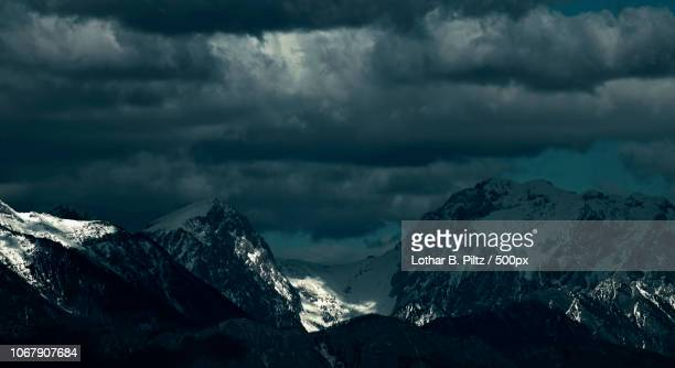 cloudy sky over snowcapped alps - ominous stock photos and pictures