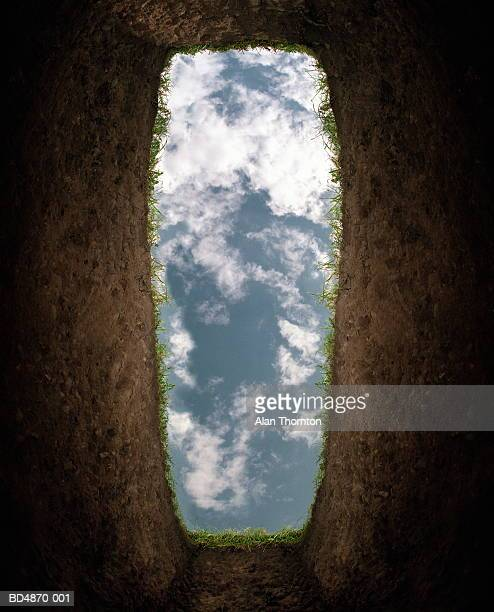 cloudy sky seen from bottom of grave (digital enhancement) - mort concepts photos et images de collection