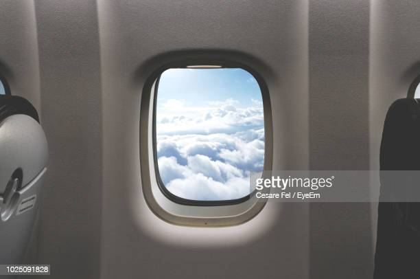 cloudy sky seen through airplane window - avion fotografías e imágenes de stock