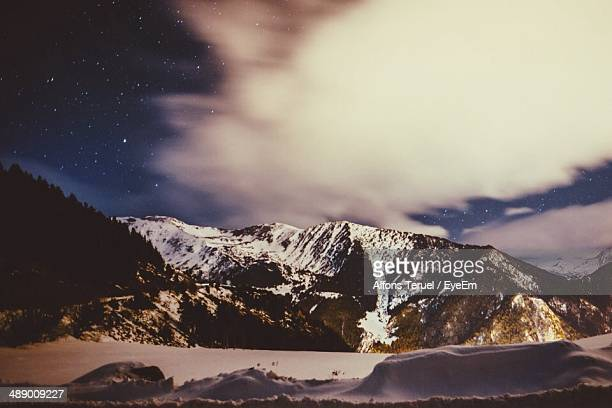 Cloudy sky with snow covered mountain and landscape