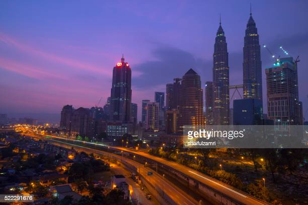 a cloudy sunrise in kuala lumpur, the capital of malaysia. its modern skyline is dominated by the 451m tall klcc, a pair of glass and steel clad skyscrapers. - shaifulzamri stock pictures, royalty-free photos & images