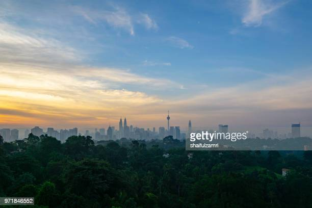 cloudy sunrise over kl tower and surrounded buildings in downtown kuala lumpur, malaysia. - shaifulzamri foto e immagini stock