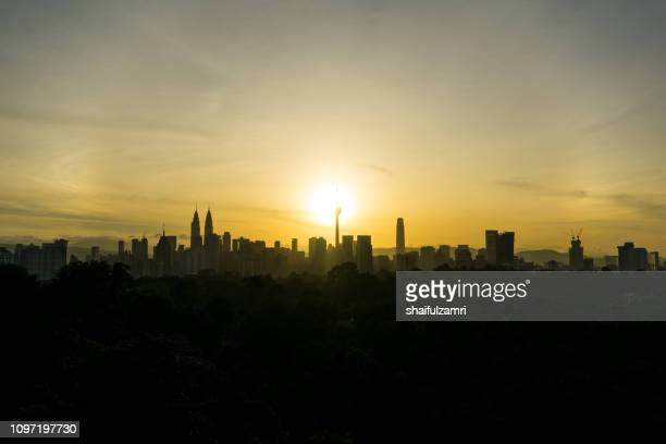 cloudy sunrise over silhouette of downtown kuala lumpur, malaysia. - shaifulzamri stock pictures, royalty-free photos & images