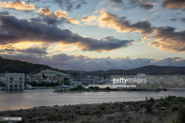 cloudy sunset above houses in alacati estuary. - emreturanphoto stock pictures, royalty-free photos & images