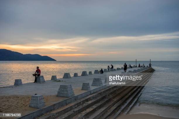 cloudy sunset view over batu feringgi beach at penang, malaysia. - shaifulzamri stock pictures, royalty-free photos & images