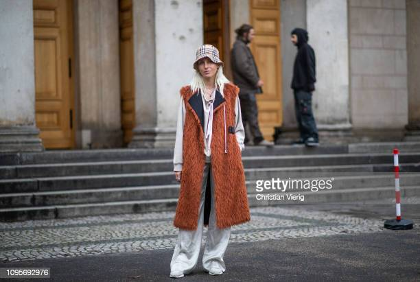 Cloudy Zakrocki is seen wearing sleeveless coat Burberry bucket hat silver flared pants during the Berlin Fashion Week Autumn/Winter 2019 on January...