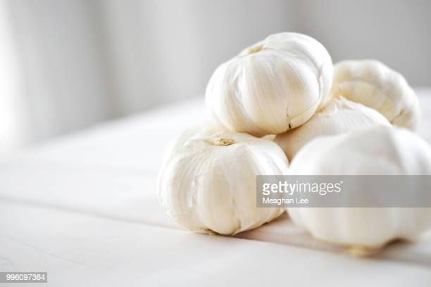 cloves of garlic stacked on table in natural light - garlic clove imagens e fotografias de stock