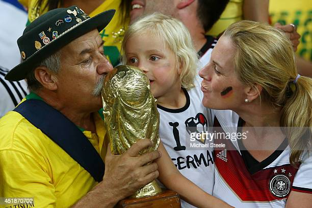 Clovis Acosta Fernandes and a young Germany fan kiss a replica of the World Cup trophy after Germany's 71 win during the 2014 FIFA World Cup Brazil...