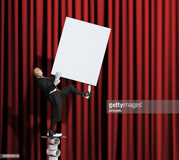 Clown balancing with blank poster in his hands