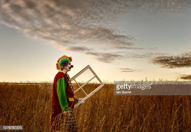 clown carrying window_1 - ian gwinn stock pictures, royalty-free photos & images