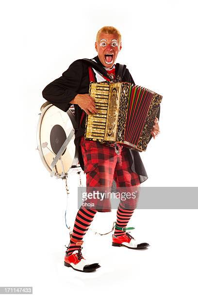 Clown doing tricks with accordion and drum on his back
