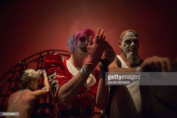 Clown dominatrix Dutchess puts on rubber gloves as she and Matlock dominate voluntary submissive Hello Kitty at a dungeon party during the DomCon LA...