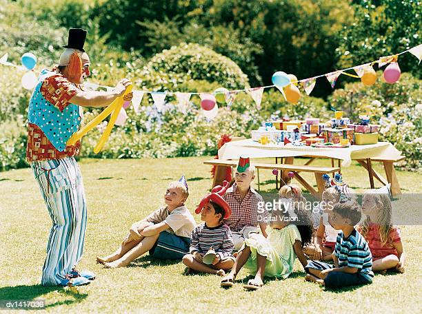 Clown Entertaining Children Sitting on the Grass at a Birthday Party