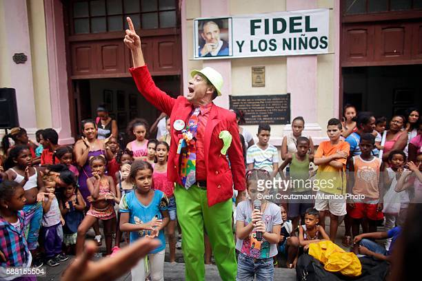 A clown entertains Cuban kids during a celebration of the 90th birthday of Cuban revolution leader Fidel Castro below a sign that bears the image of...