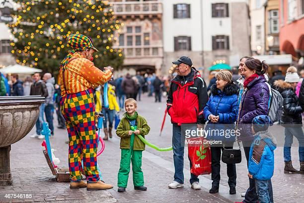 Clown folding balloon animals on square