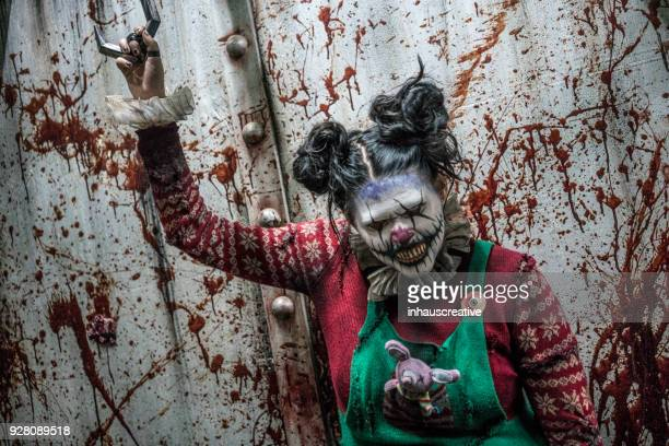 clown grabbing a hook - scary clown stock photos and pictures