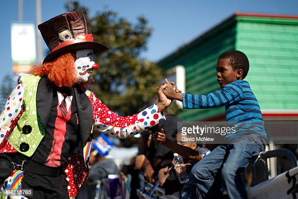 A clown greets a boy at the 29th annual Kingdom Day Parade on January 20 2014 in Los Angeles California The Kingdom Day Parade honors the memory of...