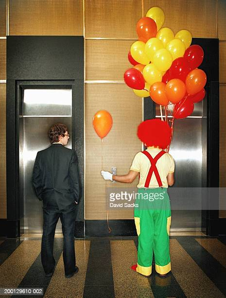 clown handing businessman balloon in lobby, rear view - multi colored suit stock photos and pictures