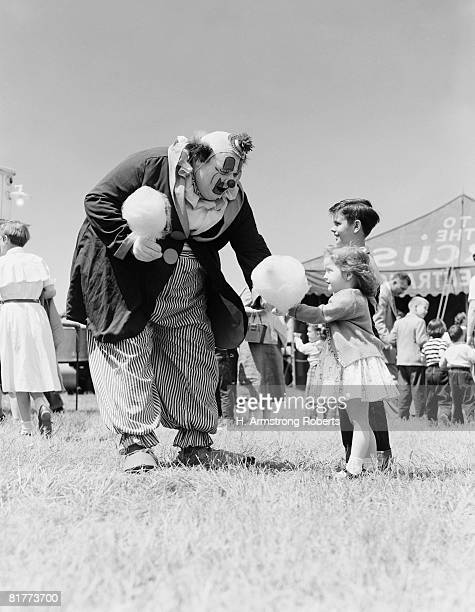 Clown handing cotton candy to children outside circus tent.