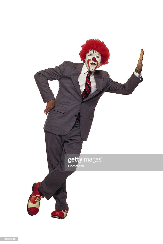 Clown in business suit leaning against wall : Stockfoto
