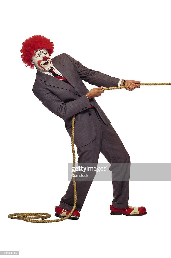 Clown in business suit tugging on rope : Stockfoto