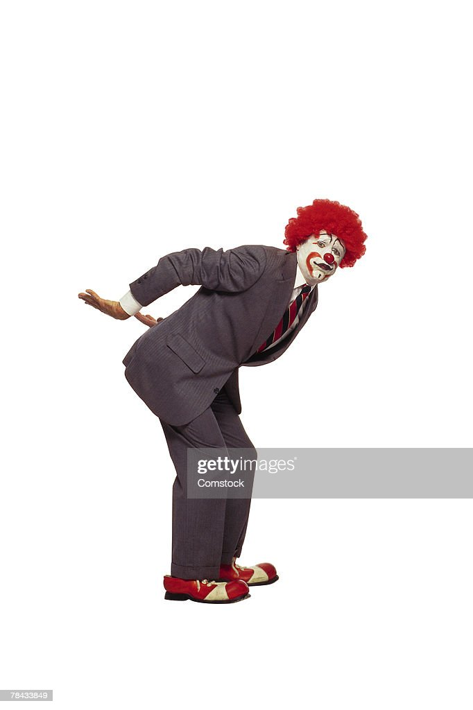 Clown in business suit with arms behind back lifting : Stockfoto