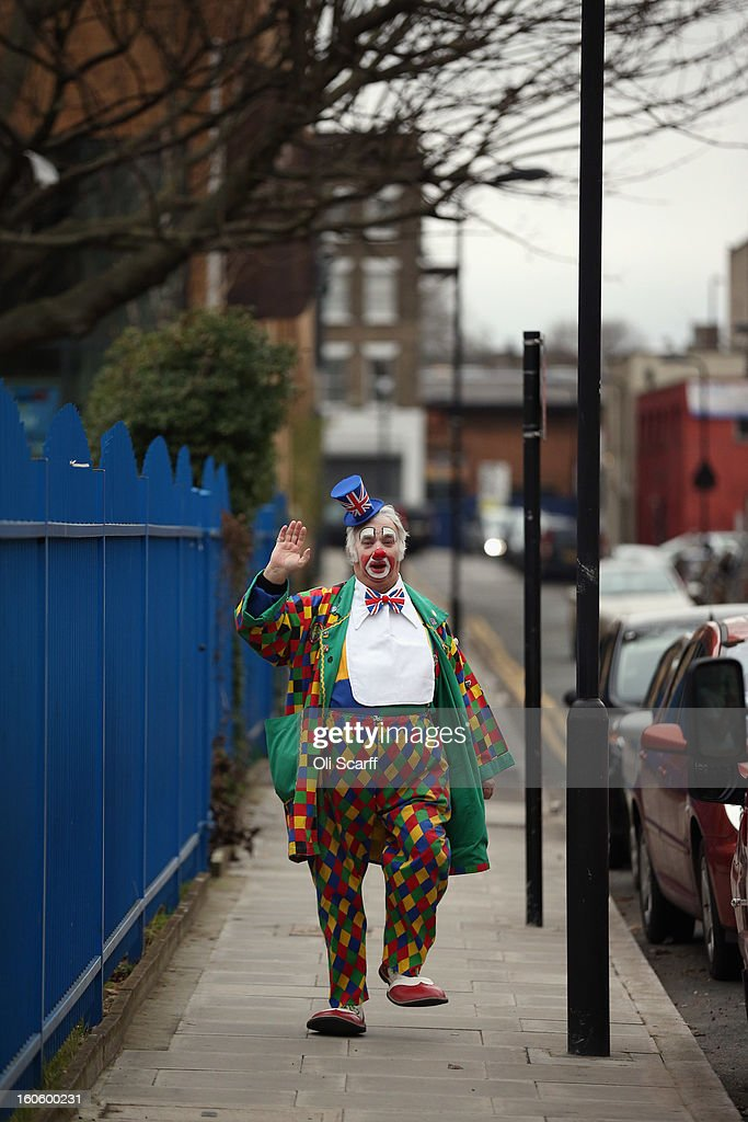 A clown in full costume arrives to attend the annual Clowns Church Service at Holy Trinity Church in Dalston on February 3, 2013 in London, England. Clowns attend the service in memory of Joseph Grimaldi (1778-1837), the most celebrated English clown who was born in London. The service has been an annual tradition since 1946 with the attending clowns usually performing for the public afterwards.