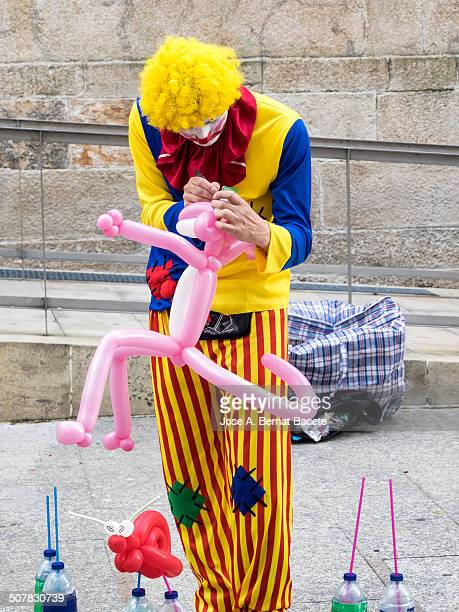 Clown in the street painting colorful balloons