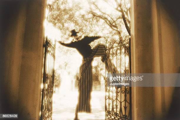 Clown on stilts going through iron gate
