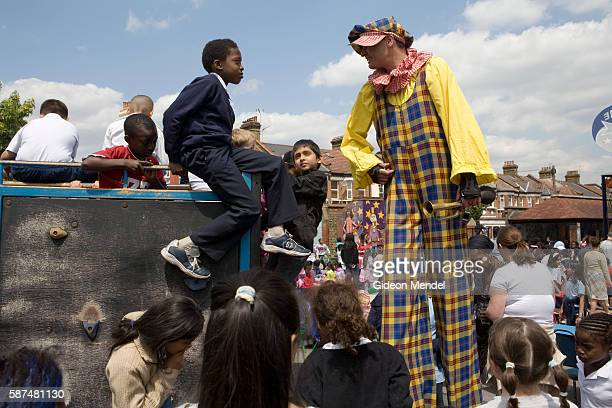 Clown on stilts greets a student at the top of a climbing frame during a special pupils picnic held at Millfields Community School to celebrate the...