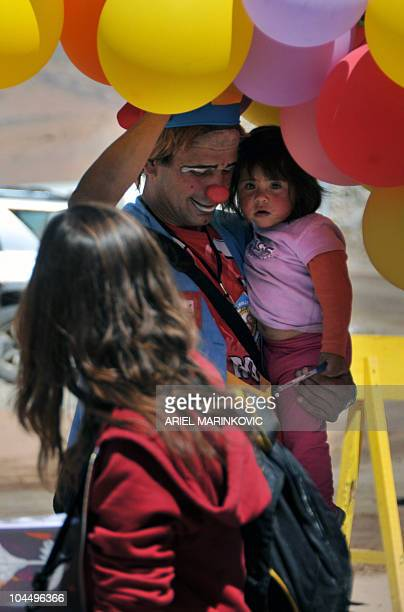 A clown plays with Camila Campillay granddaughter of Mario Gomez one of the 33 miners trapped in San Jose mine near Copiapo 800 km north of Santiago...