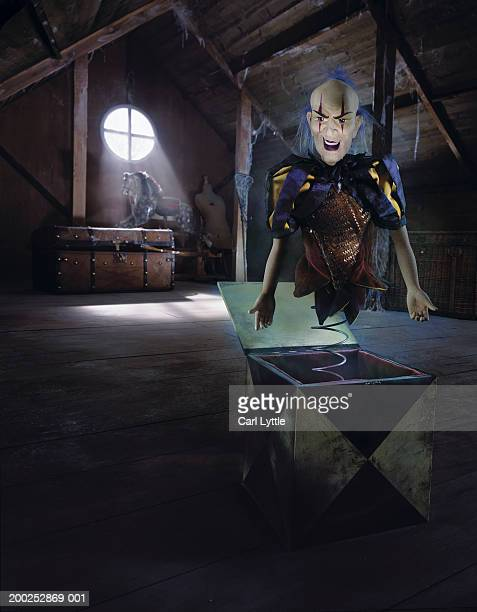 clown rising out of jack-in-the-box in attic - jack in the box stock photos and pictures