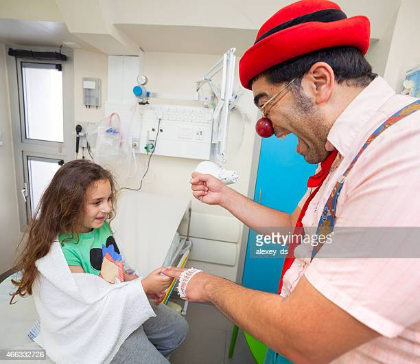 Clown shows a trick to the girl in hospital