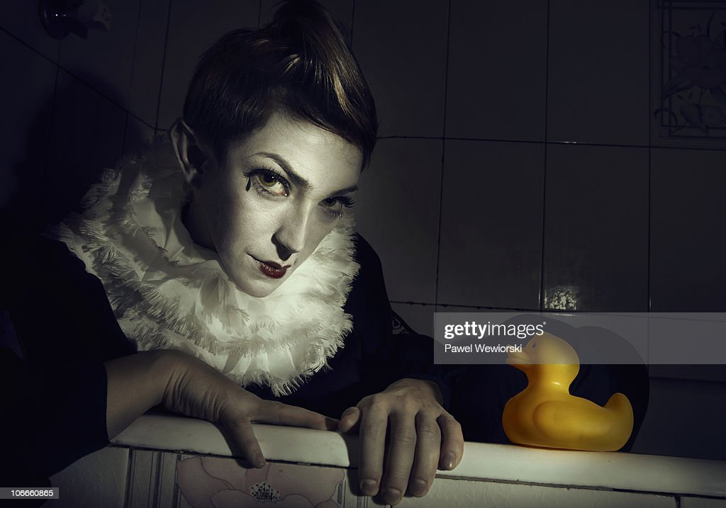 Clown with rubber duck comming out of bath tube : Stock Photo